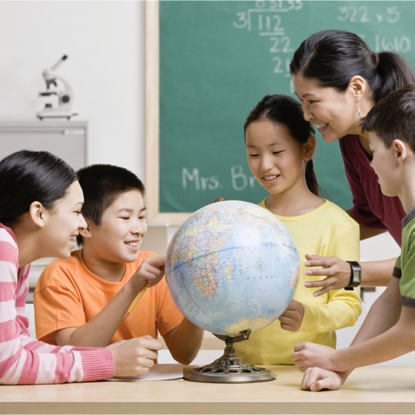 Students and teacher studying a globe of the world